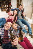 Young friends with beer bottles smiling at camera at home Stock Images