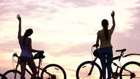 Young friends with bicycles at sunset. stock video