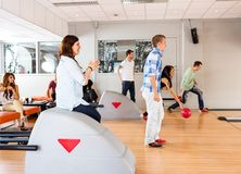 Young Friends Bowling in Club Stock Photography