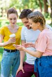 Young friends with disposable cup of coffee using smartphone. In park stock photography