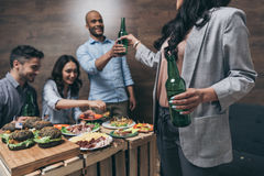 Young friends drinking beer and eating tasty dishes indoors. Happy young friends drinking beer and eating tasty dishes indoors Royalty Free Stock Photo