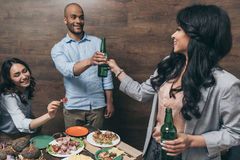 Young friends drinking beer and eating tasty dishes indoors. Happy young friends drinking beer and eating tasty dishes indoors Stock Photography