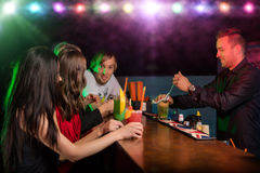 Young friends drinking cocktails together at party royalty free stock images