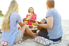 Young friends drinking rose wine on summer beach picnic Stock Images