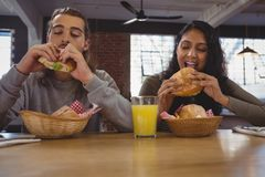 Young friends eating burgers in cafe Royalty Free Stock Image