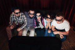 Young friends enjoy watch movie premiere on tv. Five young friends in 3d glasses sit on couch and watch movie premiere on tv with attention. Leisure Stock Photos