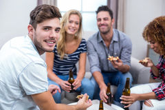 Young friends enjoying beer and pizza Royalty Free Stock Photography