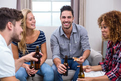 Young friends enjoying beer and pizza on sofa at home Royalty Free Stock Photo