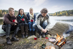 Young Friends Enjoying Camping On Lakeshore. Young friends having coffee while looking at men cooking food at lakeside camping Royalty Free Stock Image