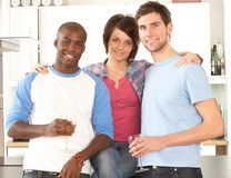 Young Friends Enjoying Glass Of Wine In Kitchen Stock Image