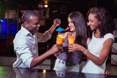 Young friends enjoying while having cocktail drinks at bar counter Royalty Free Stock Image
