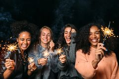 Young friends enjoying a party. Happy women holding sparklers Stock Images