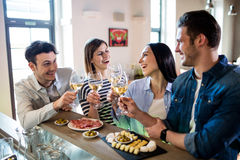 Young friends enjoying wine and food at counter royalty free stock photography