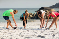 Young friends exercising on shore at beach Stock Image