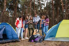 Young friends group forest tourism concept. Preparation to the musical evening. Camp stories Royalty Free Stock Images