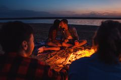 Young friends have picnic with bonfire on the beach royalty free stock photos