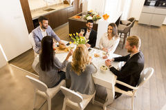 Young friends having dinner at home and toasting with white wine Royalty Free Stock Images