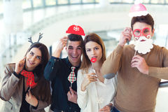 Young friends having fun holding winter artificial mustache Stock Photo