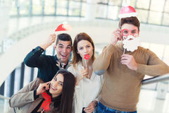 Young friends having fun holding winter artificial mustache Royalty Free Stock Photography