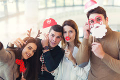 Young friends having fun holding winter artificial mustache Stock Photography
