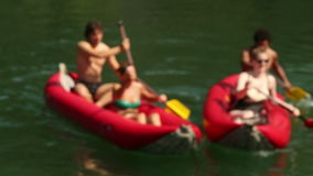 Young friends having fun riding canoe on river stock video footage