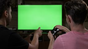 Young friends having fun with wireless joysticks competing with each other playing video games on chroma key green screen -. Young friends having fun with stock footage