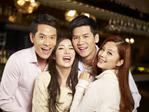 Young friends having good time in pub. Young asian friends couples enjoying party in pub Royalty Free Stock Image