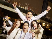 Young friends having good time in pub. Young asian friends couples enjoying party in pub Stock Photography