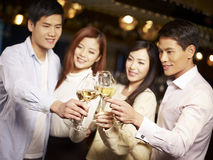 Young friends having good time in pub. Young asian friends couples enjoying party in pub, focus on hands and glasses Stock Image
