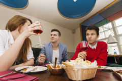 Young friends having meal at restaurant Stock Photos