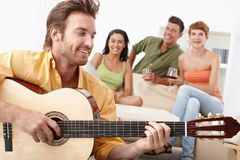 Young friends having party. Young happy friends having party, one playing guitar, the others listening Stock Photos