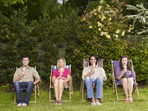 Young Friends With Icecreams On Deckchairs At Garden Royalty Free Stock Images