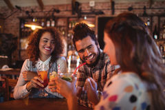 Young friends interacting with each other having drinks Royalty Free Stock Images