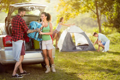 Young friends just came to camping trip. Unpacking royalty free stock photo