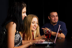 Young friends with laptop in a bar Royalty Free Stock Photo