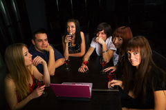 Young people with laptop in a night bar Stock Photos