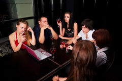 Young friends with laptop in a bar. Royalty Free Stock Images
