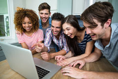 Young friends laughing while looking in laptop on table Stock Images