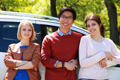 Young friends  leaning on the car Royalty Free Stock Image