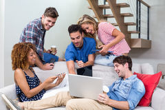 Young friends looking in laptop while sitting on sofa. Happy young friends looking in laptop while sitting on sofa at home Royalty Free Stock Photography