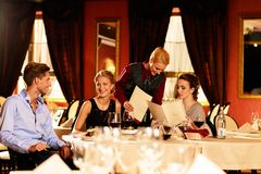 Young friends in a luxury restaurant. Group of young friends with menus choosing in a luxury restaurant royalty free stock photos