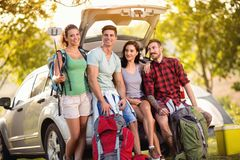 Young friends make selfie photo with smartphone in the trunk on camping trip. Group of young hipster friends make selfie photo with smartphone in the trunk on stock photos