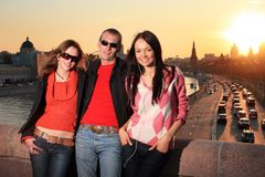 Young friends in Moscow. Man and two beautiful young women in Moscow city at sunset. Russia Royalty Free Stock Images