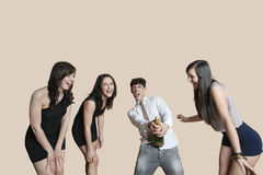 Young friends opening champagne bottle over colored background Stock Photos