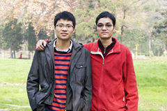 Young friends in park. Two asian young men in autumn park Royalty Free Stock Photography