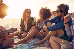 Young friends partying at the beach. Portrait of group of young friends having a party on the beach in evening. Men and women drinking beers and listening to Royalty Free Stock Photos
