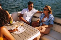 Young friends partying on a boat. Group of young men and women enjoying at yacht party. Young friends partying on a boat. They are sitting at the back of the Royalty Free Stock Photography
