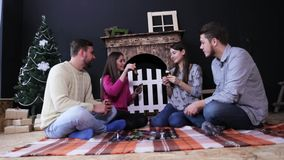 Company of friends play in board game with cards on the plaid in a box. Fireplace and Christmas tree background. Young friends play in board game with cards on stock video