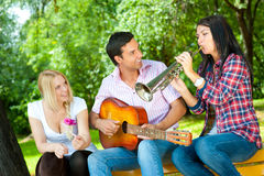 Young friends play the guitar and trumpet Stock Photos