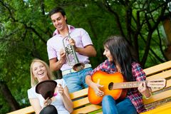 Young friends play the guitar and trumpet Stock Image